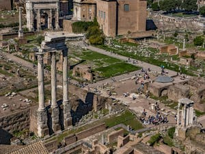 The three columns of the Castor and Pollux Temple with, on the right, with its half circular plate roof, the Jules Cesar Temple in the Roman Forum in Italy