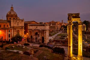 Roman Forum by night, Septimius Severus Triomphal Arch and Concord Temple three columns in Rome in Italy